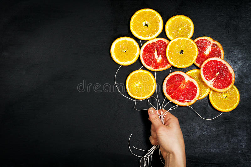 Food Art. Fruit slices on a dark Chalkboard Background with strings. Balloons from fruit slices. Healthy life, detox concept. stock image