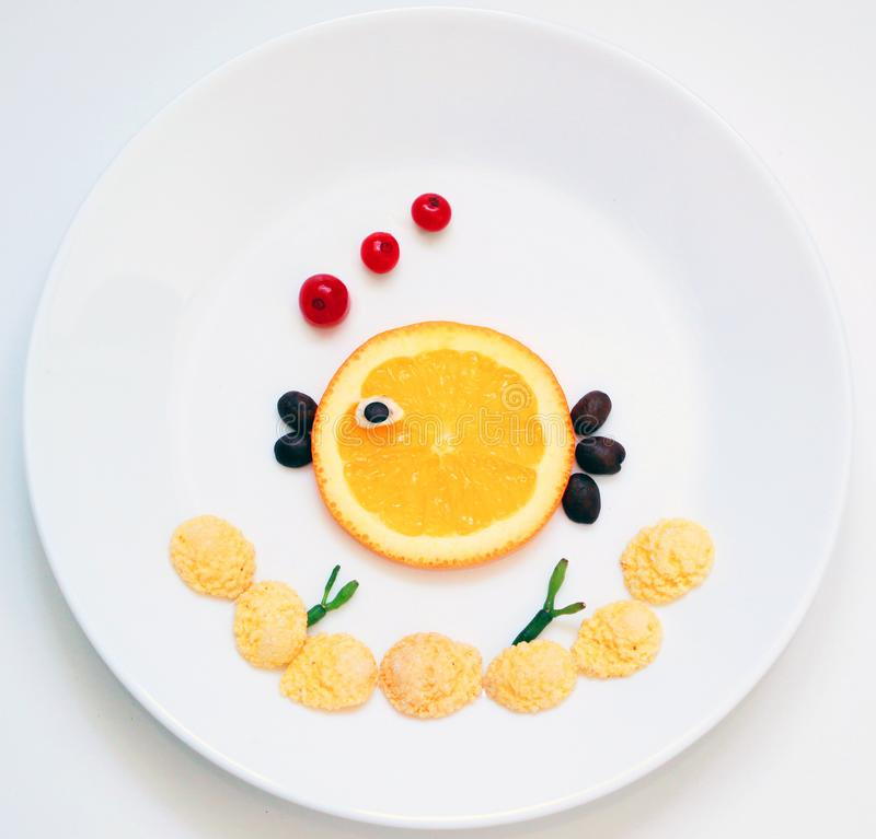 Funny breakfast for kids, fish. Food art. Funny breakfast for kids. Fish and seaweed from flakes and fruits on the white plate royalty free stock images