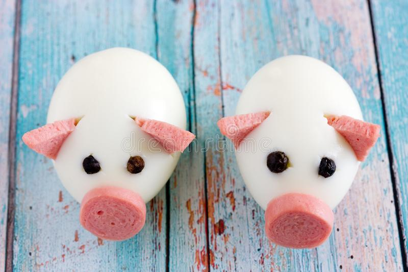Food art idea for kids - funny edible piggies from boiled eggs. Sausage and black pepper stock photography