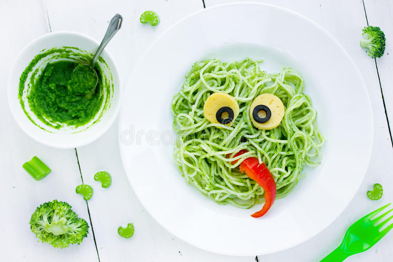 Food art idea for kids green monster from spaghetti, olives and royalty free stock photography