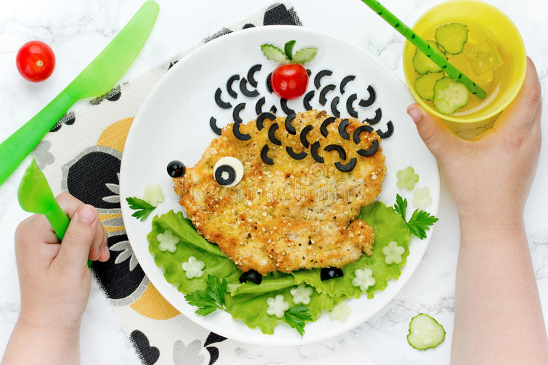 Food art idea for kids lunch - schnitzel with vegetables shaped stock photography