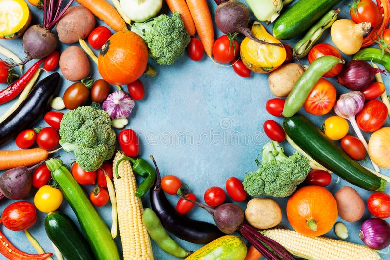 Food background with autumn farm vegetables and root crops on blue table top view. Healthy and organic harvest. royalty free stock photography