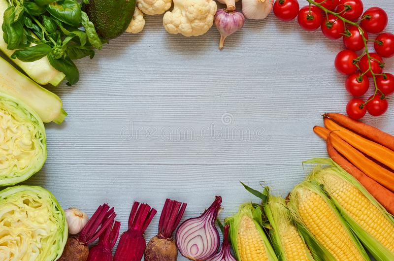 Food background with copy space for text. Fresh organic vegetables on the gray table: cherry tomatoes, zucchini, beet, garlic stock photos
