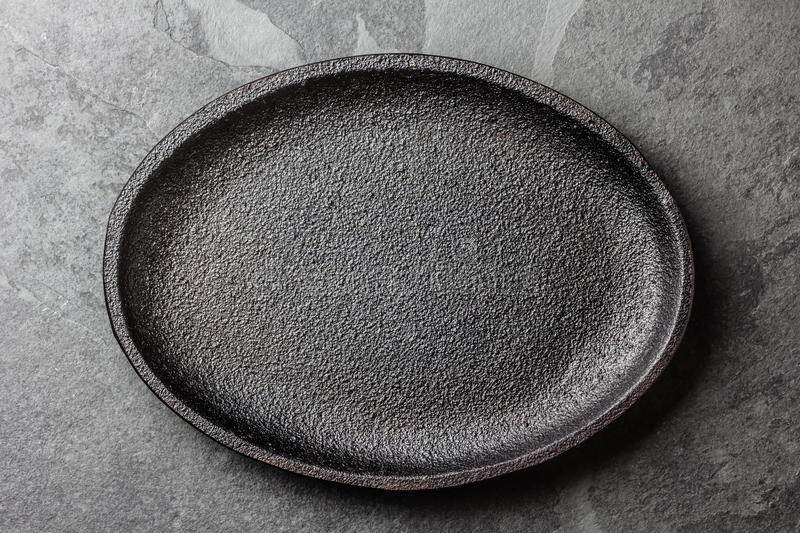 Food background. Empty cast iron black plate royalty free stock image