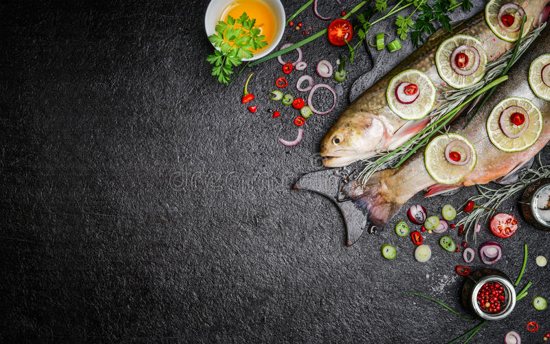 Food background for fish dishes cooking with various ingredients. Raw char with oil, herbs and spices on cutting board , top view. stock photo