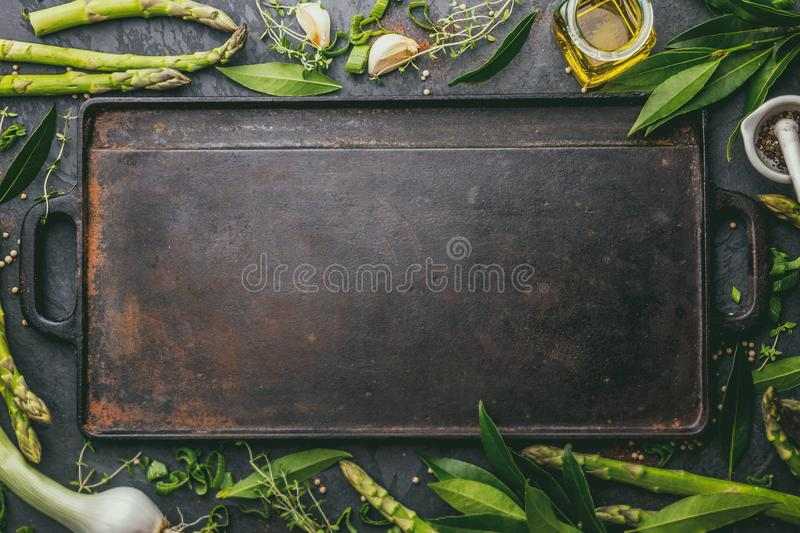 Food background with free space for text. Herbs, olive oil, spices around cast iron frying board. Top view.  stock photos