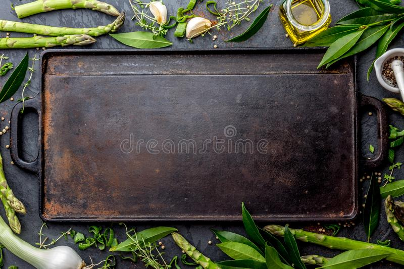 Food background with free space for text. Herbs, olive oil, spices around cast iron frying board. Top view.  stock image