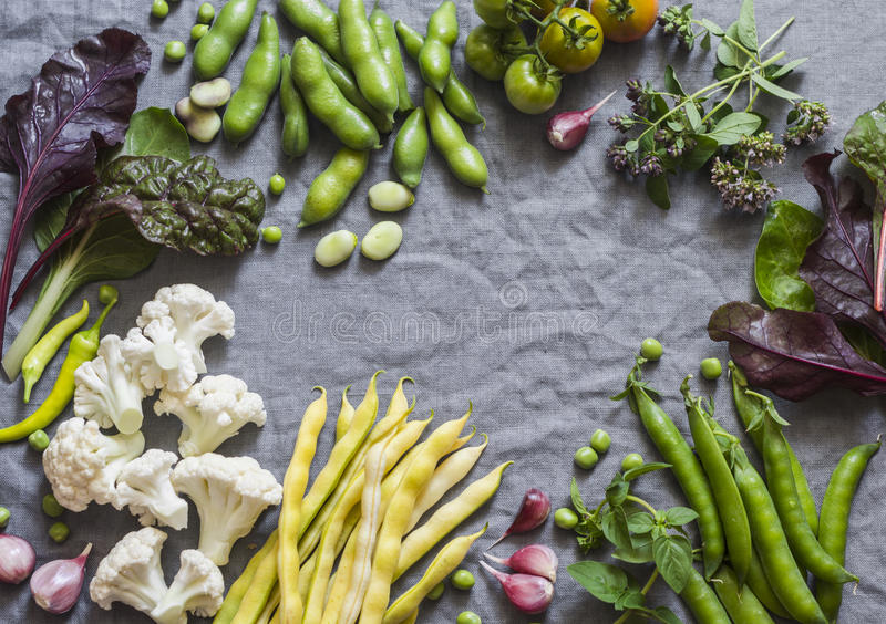 Food background. Fresh garden vegetables on grey background, top view. Cauliflower, beans, peas, chard, fava beans - organic veggi royalty free stock photos