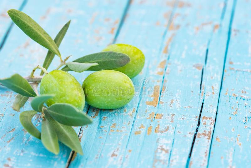 Food background with fresh green olives on brunch on rustic blue wooden table royalty free stock image