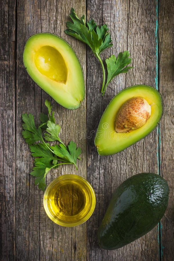 Food background with fresh organic avocado, lime, parsley and olive oil. On old wooden table, top view royalty free stock photo