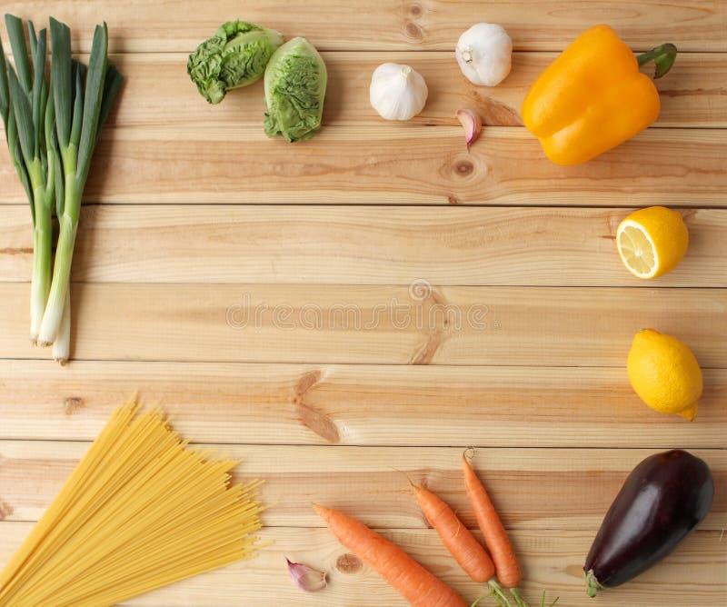 Food background. Fresh organic raw carrots, lettuce, paprika, lemons, eggplant, potatoes, spaghetti, vegetables on a light wooden stock photos