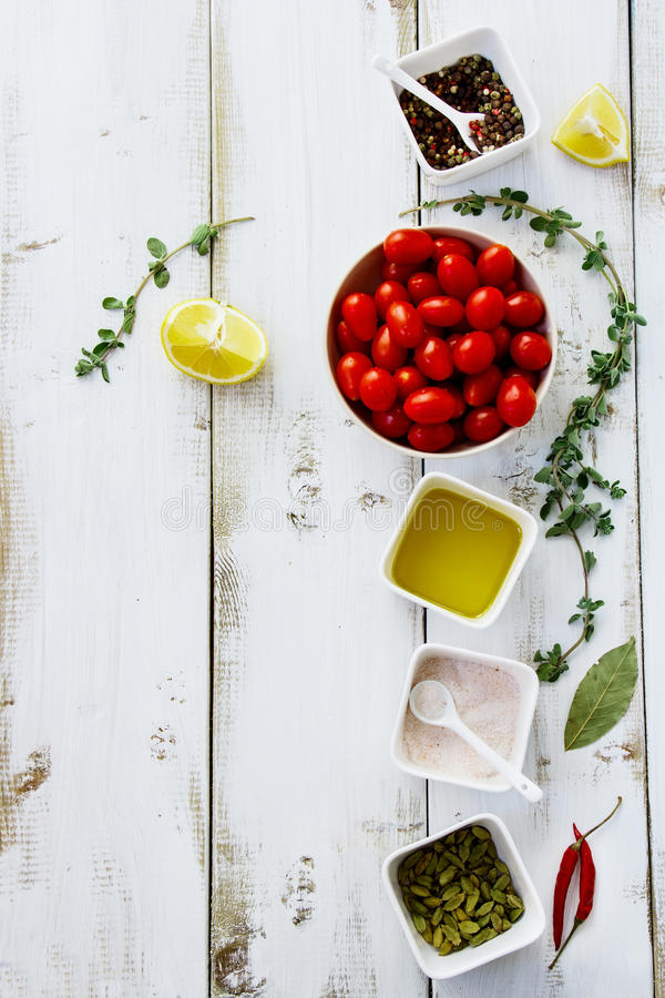 Food background. Fresh tomatoes with herbs, spices, olive oil, pink salt and lemons on white wooden board with copy space. Food background. Top view royalty free stock photography