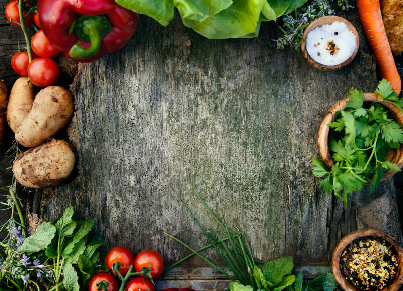Food background. Healthy food ingredients background. Vegetables, herbs and spices. Organic vegetables on wood royalty free stock images