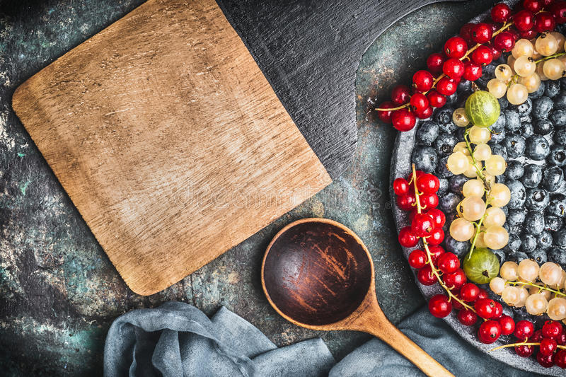 Food background for healthy recipes with various colorful berries, cooking spoon, bowls and napkin , top view. Frame royalty free stock image