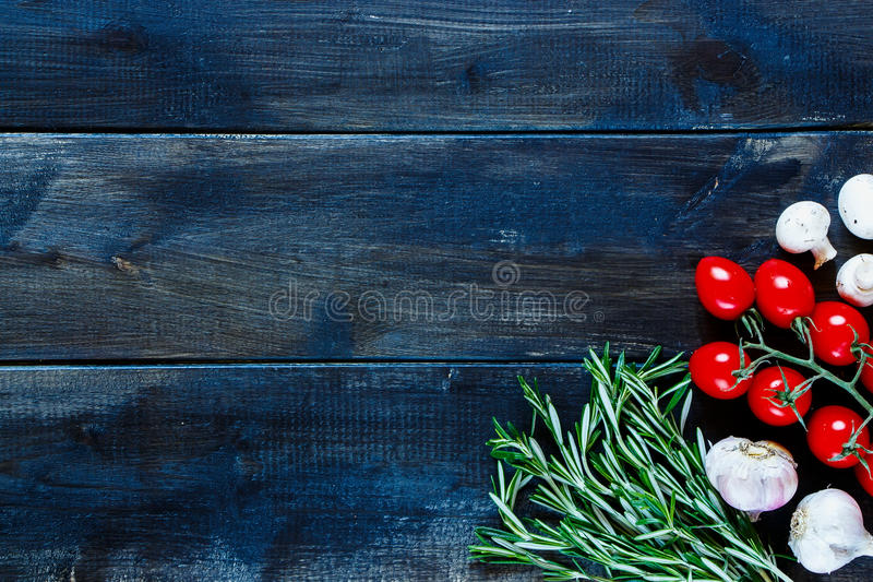 Food background. Food ingredients background with tomatoes, garlic, rosemary and mushrooms over dark wooden board. Health, cooking or diet concept. Top view stock photo