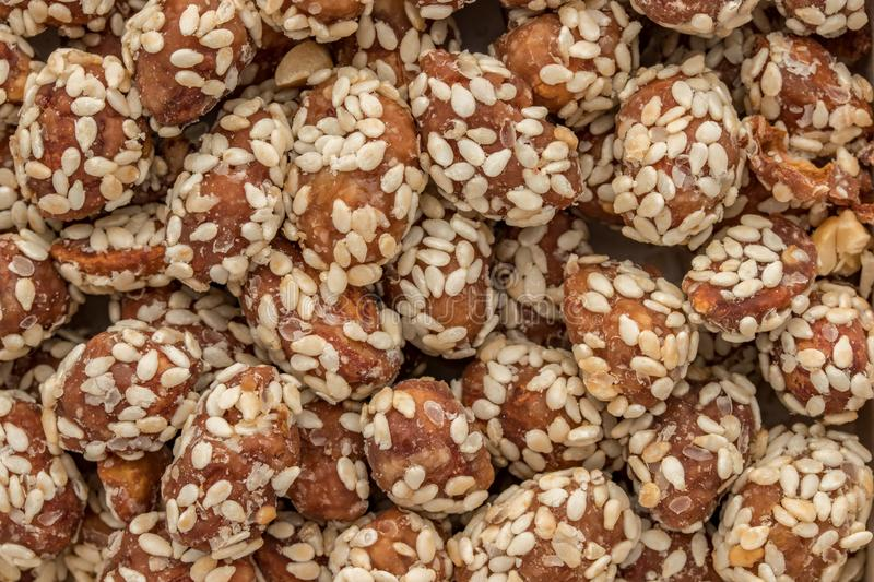 Food background made of peanuts covered with glaze and sprinkled with sesame seeds royalty free stock image