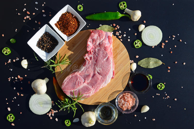 Food background. Meat on a cutting board and pepper, bay leaf, rosemary, onions, Himalayan salt, olive oil, soy sauce on a black. Background. The template for royalty free stock photography