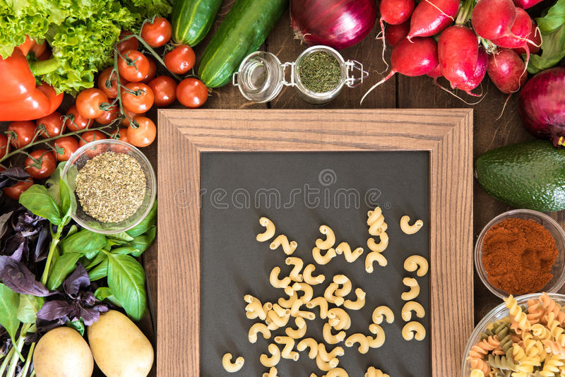 Food background with natural vegetables, spices and two types of Italian pasta on chalkboard royalty free stock images