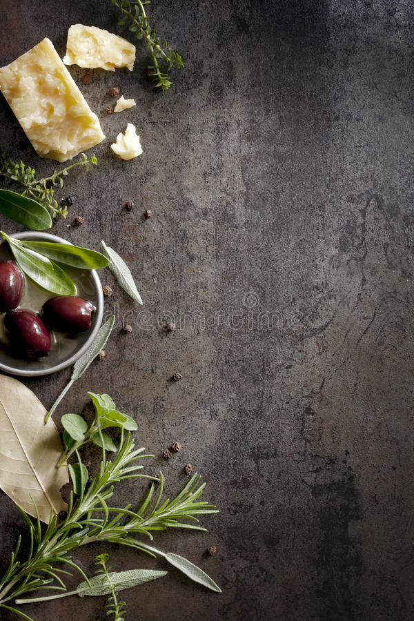 Food Background. With parmesan cheese, fresh herbs and olives, over dark slate. Lots of copy space royalty free stock photography