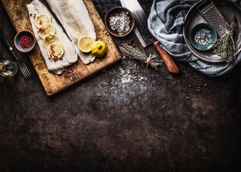 Food background with raw cod fillet with lemon slices and herbs on rustic background with cutting board and knife, top view. Fish. Cooking preparation. Healthy stock image