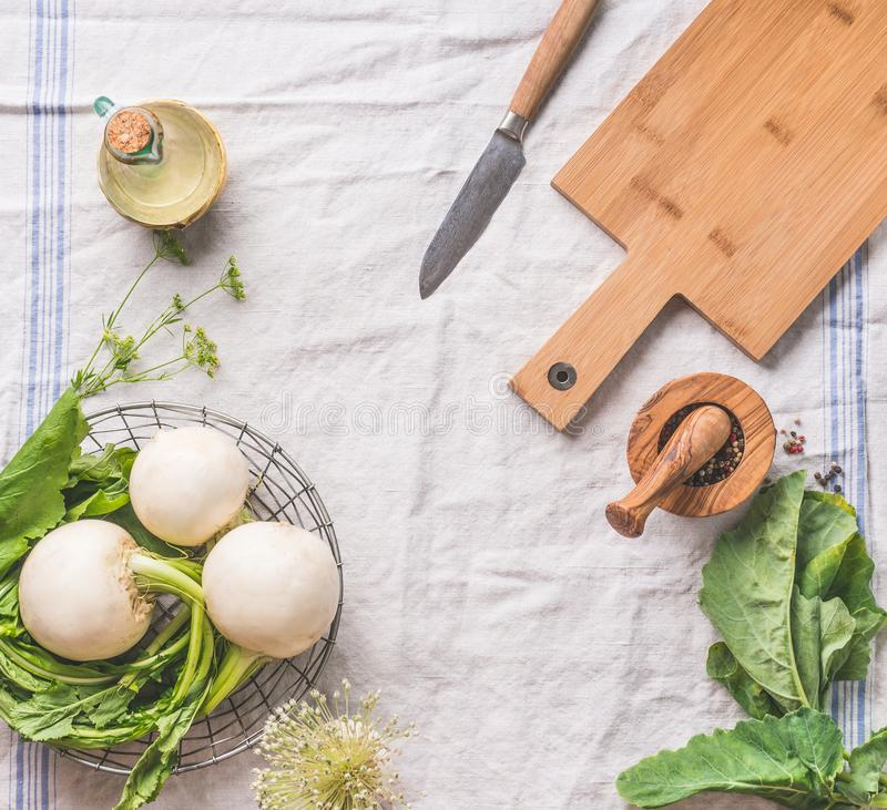 Food background with raw young turnip  with greens on light kitchen table with cutting board and knife, top view. Healthy stock photo