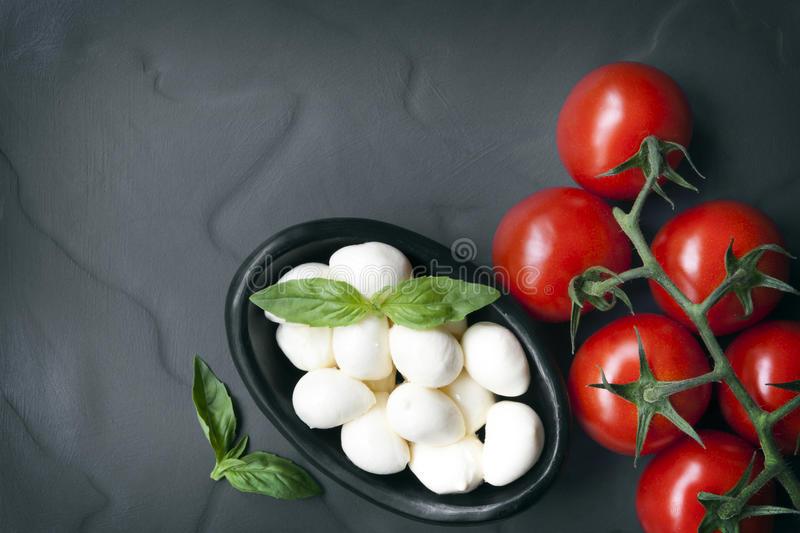 Food Background Slate with Baby Mozzarella Balls Vine Tomatoes a royalty free stock images