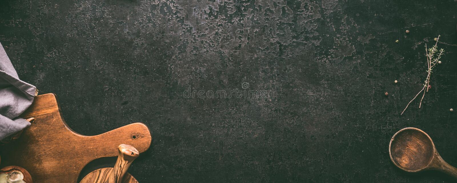Food background. Top view of dark rustic kitchen table with wooden cutting board, cooking spoon and seasoning. Banner or template. With copy space for your royalty free stock images
