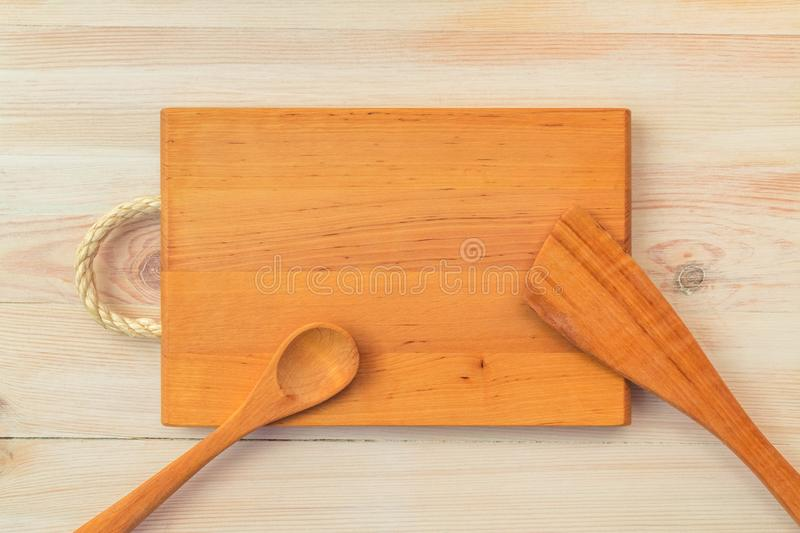 Food background. Top view of empty wooden cutting board, spoon and spatula on planks vintage table with copy space stock photos