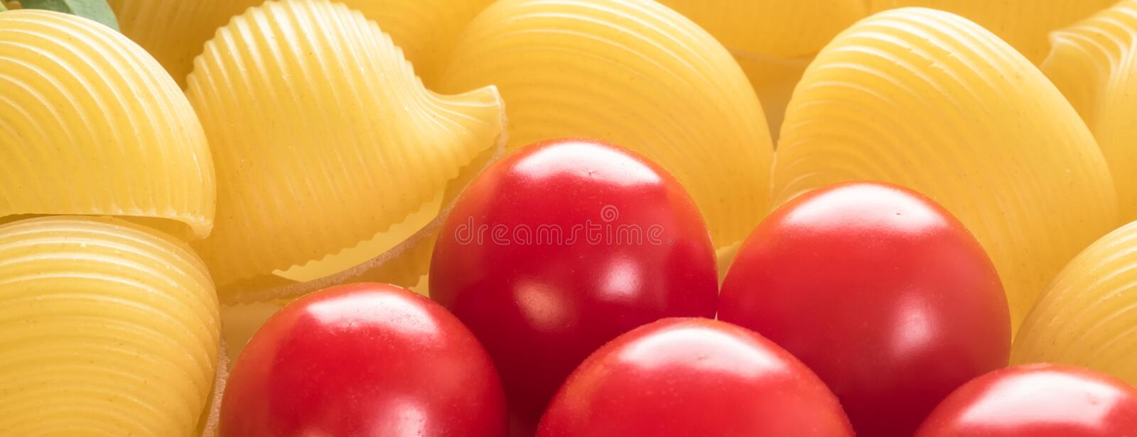 Food background Uncooked Macaroni Lumaconi. Close-up macro red Cherry Tomatoes in flower form Concept set of ingredients for Pasta internet web banner for site royalty free stock image