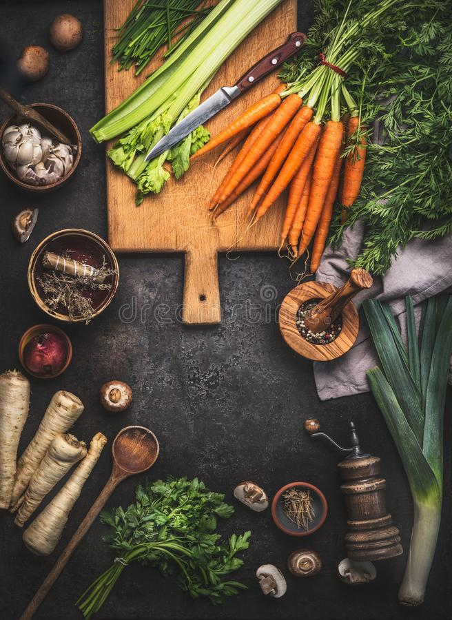 Food background with various organic farm vegetables on dark rustic table with kitchen utensils, herbs and spices, top view. Frame stock images