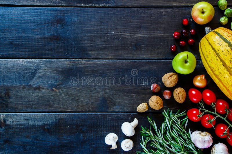Food background. Vegetables, fruits, nuts and herbs on dark wood. Healthy food ingredients background with space for text. Health or diet concept. Top view royalty free stock image