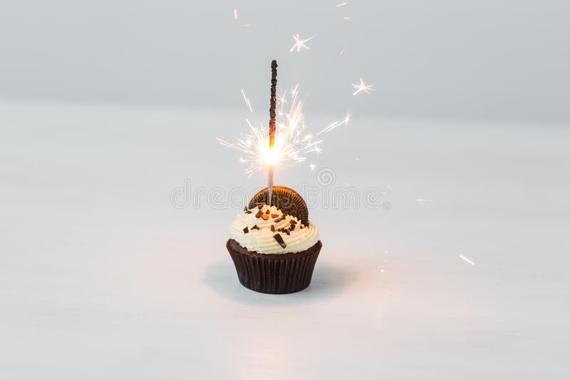 Food, bakery, holiday, happy birthday and desserts concept - delicious cupcake with sparkler and cookie on white table stock photos