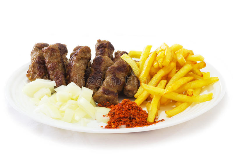 Food of the Balkans. Cevapi - Traditional Food of the Balkans. Minced Meat Cooked on the Barbecue with Fresh Onion royalty free stock image