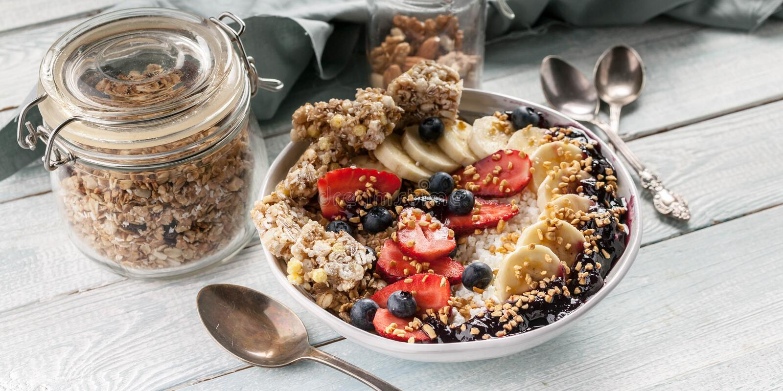 Food banner. Organic breakfast. Cottage cheese, granola, bananas, strawberries, blueberries and puffed rice. Wooden table stock images
