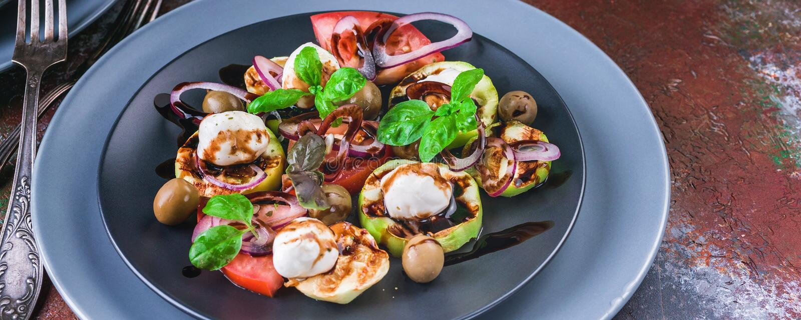 Food banner salad with grilled vegetables, mozzarella, olives, red onion, basil and balsamic sauce on a rust background. stock image