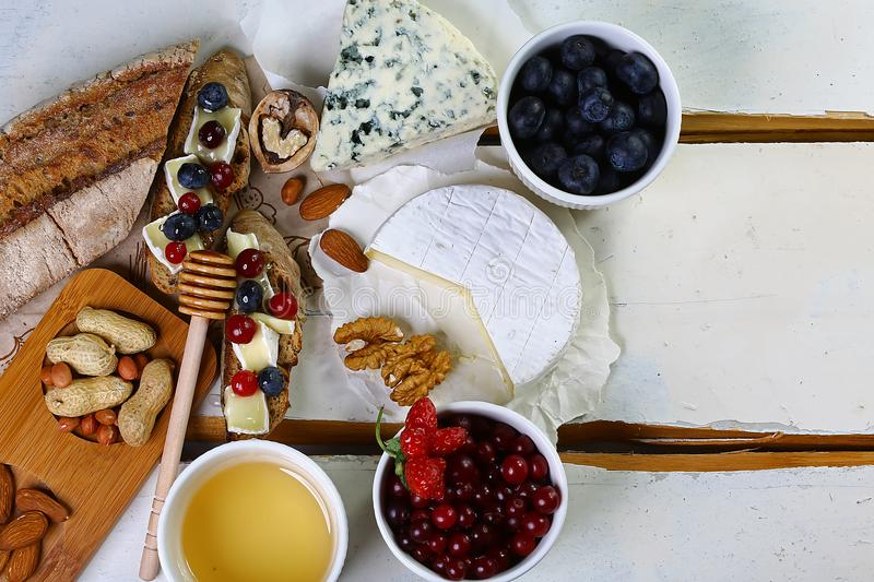 Food banner - Two toasts or bruschetta with blueberries and cranberries on cream cheese camembert, DorBlu, salty blue cheese nuts,. On rustic background. Top stock photos