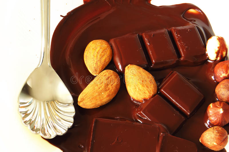 Food. Bar of chocolate that melts with almonds and hazelnuts over and dessert spoon stock photos