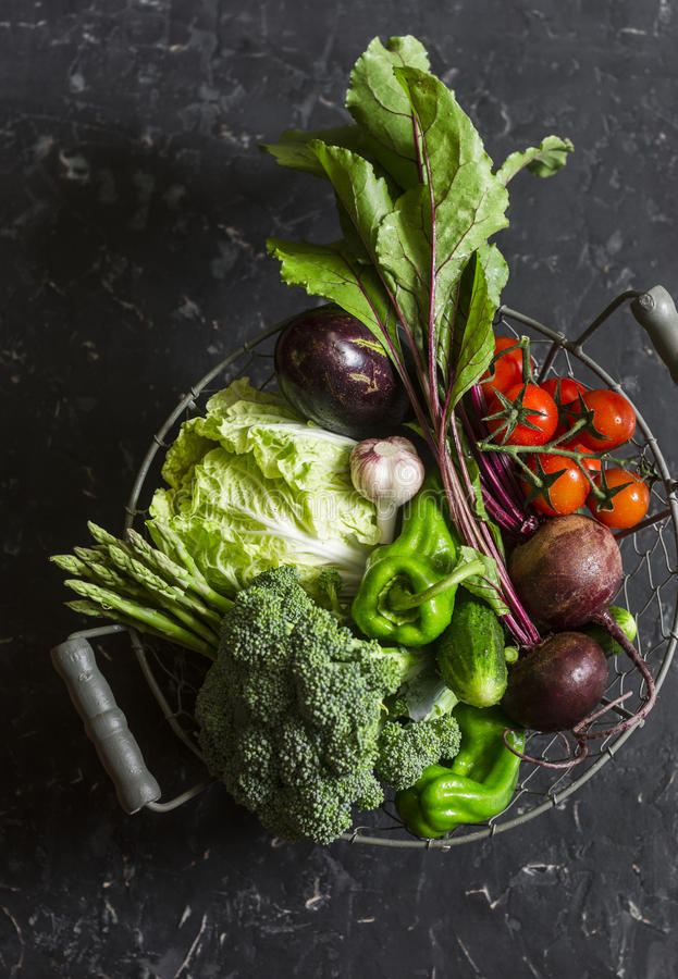 Food basket with fresh garden vegetables - beets, broccoli, eggplant, asparagus, peppers, tomatoes, cabbage on a dark table royalty free stock photo