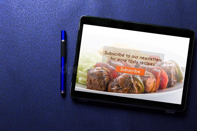 Food blog subscribtion concept on tablet screen with blue pen on blue pattern royalty free stock image