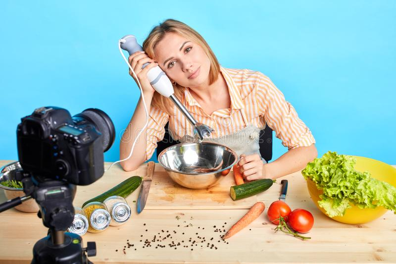 Food blogger holds hand blender, ready to start shooting new video for cooking blog stock image