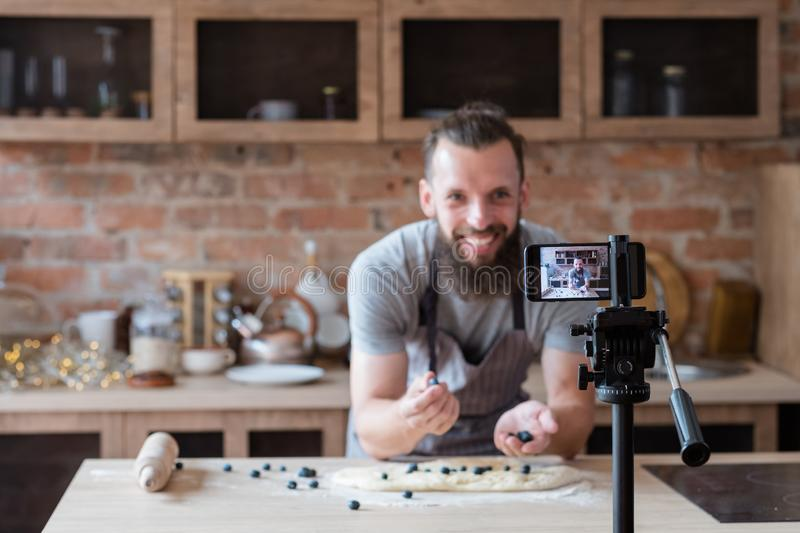 Food blogger lifestyle work man cook video streaming. Food blogger lifestyle and working process. bearded hipster man video streaming about cooking pie. social royalty free stock photography