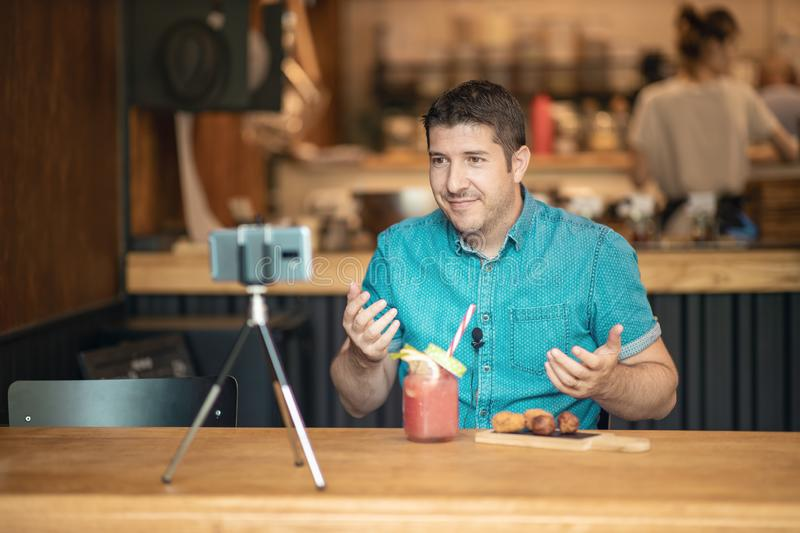 Food blogger streaming live on social media - Man creating blog video content using smart phone camera on a tripod stock image