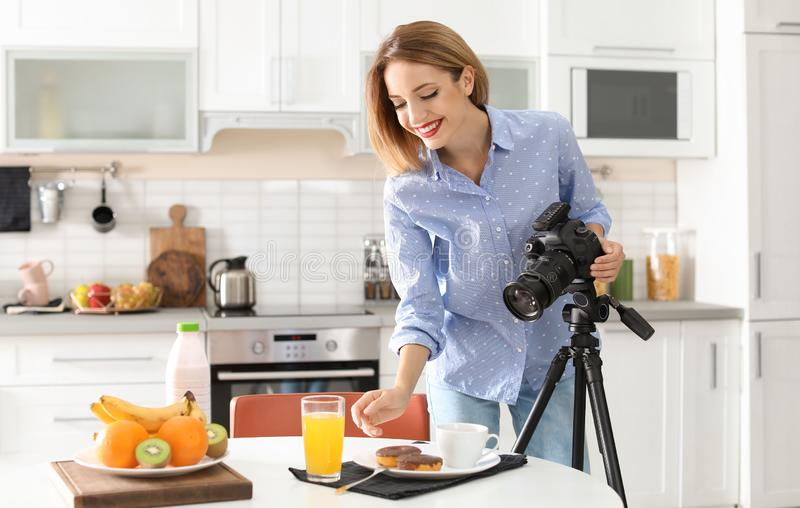 Food blogger taking photo of breakfast. In kitchen stock image