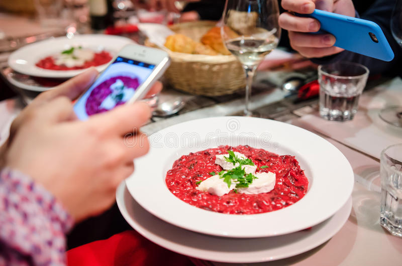 Food bloggers. In restaurant taking photos of the dishes with their smartphones royalty free stock images