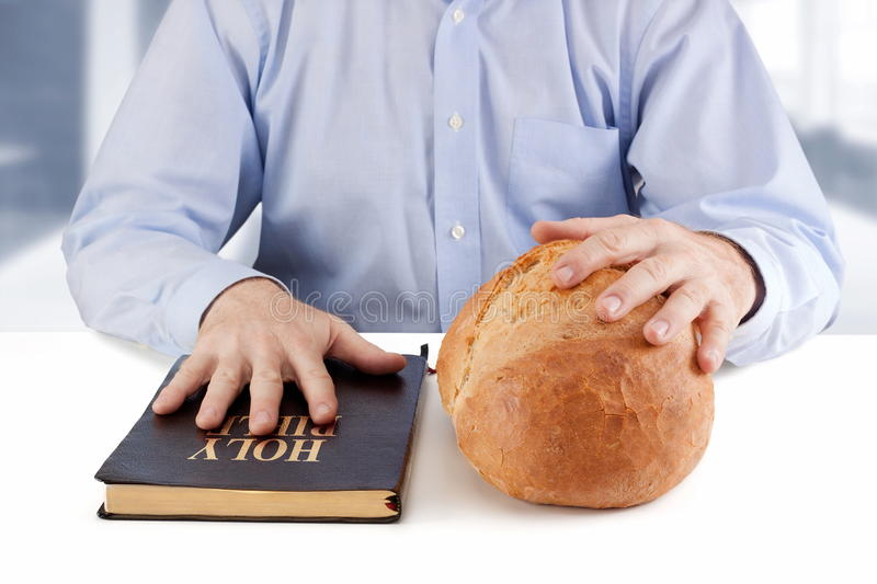 Food for body and soul. Man holding a Bible and bread on the table royalty free stock image