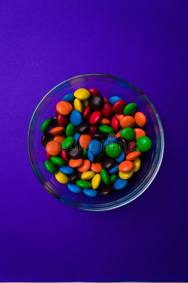 Bowl filled with multicolored candy on a purple background. Glass bowl filled with blue, orange, yellow, red, brown and green candy on a purple background seen stock photography