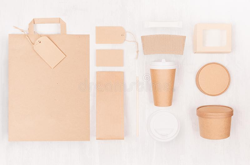 Food branding identity mockup in light modern style - blank coffee cup, packet, bag, box, label, card of brown paper on wood. stock image