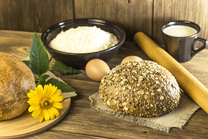 Food, breakfast. Rustic still life. Fresh bread baked in the bakery, chicken eggs, cottage cheese and milk on the background of t royalty free stock images