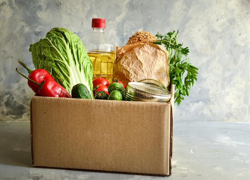 Food in a cardboard box. Food donation or food delivery concept. Light background. Free space for text. Oil, cabbage. Food in a cardboard box. Food donation or royalty free stock photography