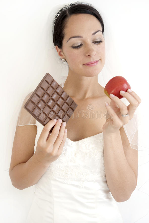 Food choices. Bride holding healthy and unhealthy food - dieting wedding concept stock image